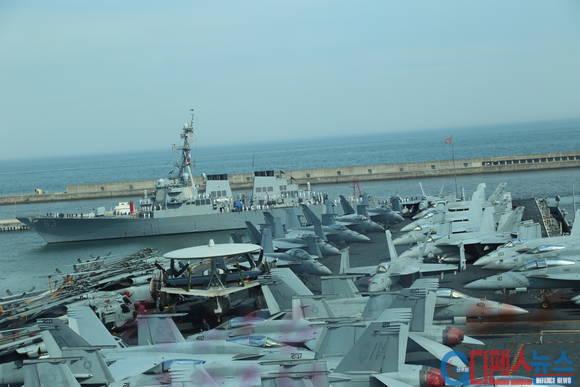 부산에 입항한 조지 워싱톤 항공호함 전단 - 갑판에 첨단 항공기들이 즐비하게 도열해 있다. 그 뒤로 항모전단을 호위하는 이지스함이 입항하고 있다.