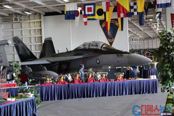 항공모함 내부 갑판에서 F-18 슈퍼호넷을 배경으로 연회 준비가 한창이다. 첨단 전투기를 배경으로 식사를 즐기는 모습을 보니 미국의 힘과 여유가 느껴진다.
